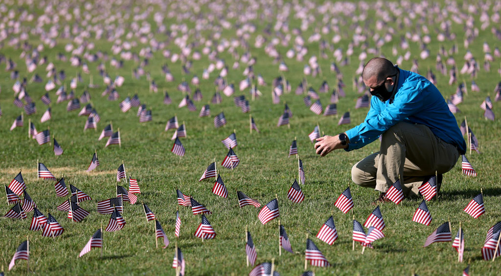 WASHINGTON, DC - SEPTEMBER 22: Chris Duncan, whose 75 year old mother Constance died from COVID on her birthday, photographs a COVID Memorial Project installation of 20,000 American flags on the National Mall as the United States crosses the 200,000 lives lost in the COVID-19 pandemic September 22, 2020 in Washington, DC. The flags are displayed on the grounds of the Washington Monument facing the White House. (Photo by Win McNamee/Getty Images)